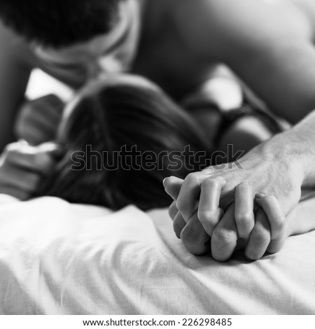 Young passionate couple making love in bed.  Focused on hand - stock photo
