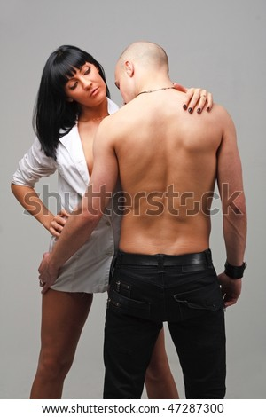 Young passionate couple standing on a grey background - stock photo