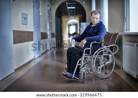 Young patient in a wheelchair in hospital - stock photo