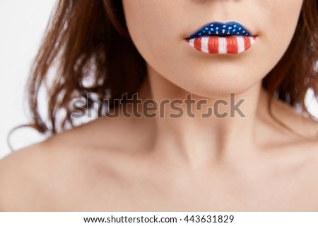 Young patriot white girl painted her lips in colors of American Flag celebrating National Independence Day on 4th of July.Close up macro - stock photo