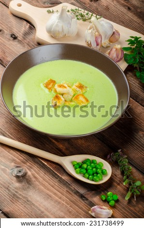 Young pea soup with small garlic croutons - stock photo