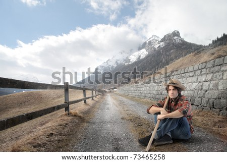 Young peasant sitting on a countryside road - stock photo