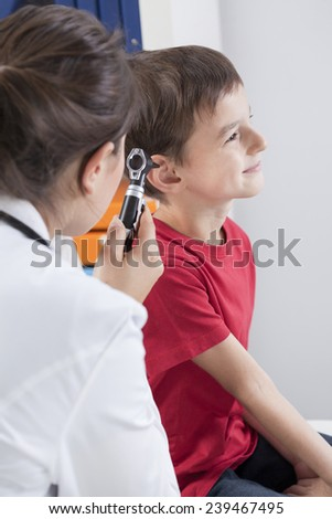 Young pediatrician checking the little man by otoscope - stock photo