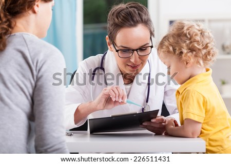 Young pediatrician talking with a girl patient - stock photo
