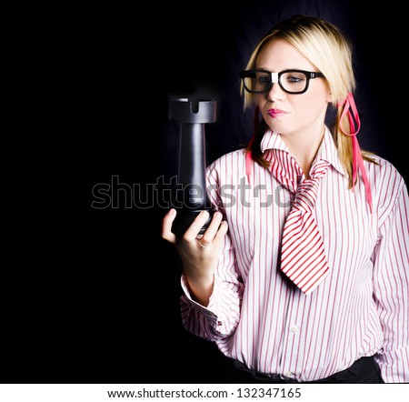 Young pensive caucasian business woman holding oversized pawn chess piece in a best practise strategy concept on black background