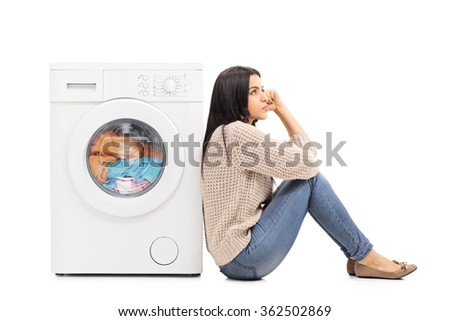 Young pensive housewife sitting on the floor waiting for the washing machine to finish isolated on white background - stock photo