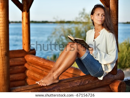 Young pensive lady with book in summerhouse on sunset - stock photo