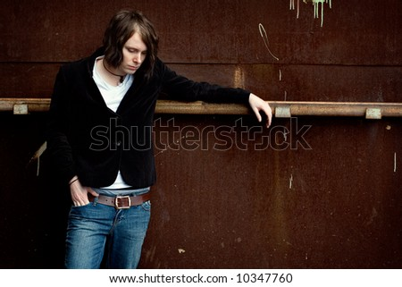 Young pensive man against a rusty wall