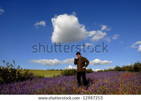 young pensive man among flowers and the sky - stock photo