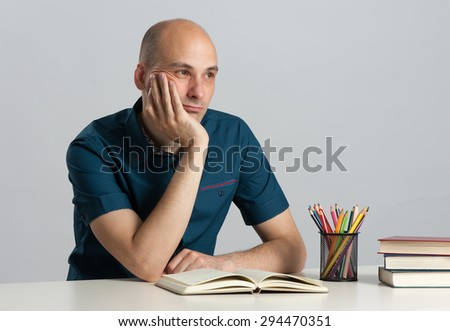 Young pensive man sitting at the desk with book - stock photo