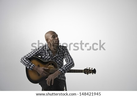 Young pensive man with guitar sitting against gray background - stock photo