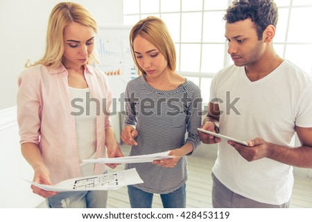 Young pensive people of different nationalities are discussing business affairs while examining papers - stock photo