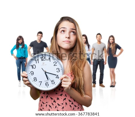 young pensive woman holding a clock on white - stock photo
