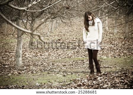 Young pensive woman in dark scenery. - stock photo