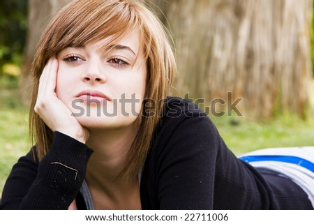 Young pensive woman laying in nature - stock photo