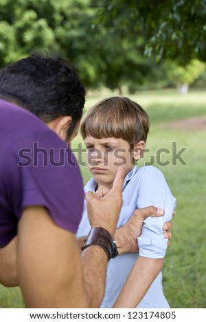 Young people and difficult parenthood, upset father scolding scared son while holding his arm. Waist up, focus on background - stock photo