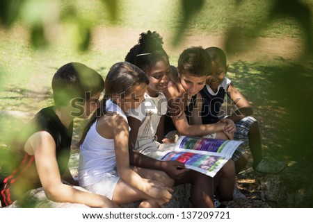 Young people and education, two little girls and boys reading book in city park - stock photo