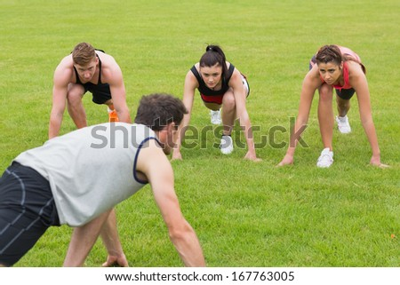 Young people and instructor doing stretching exercise on grass at the park - stock photo