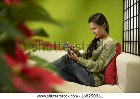 Young people and technology, Asian girl typing on digital tablet, pretty female student using computer and sitting on sofa at home - stock photo