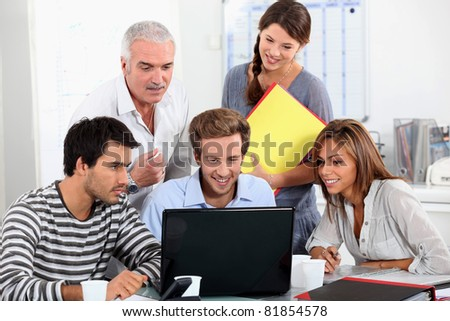 Young people and their manager sitting round a laptop computer - stock photo