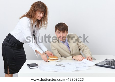 Young people are having dinner at the workplace in a light office - stock photo