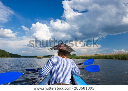 Young people are kayaking on a river in beautiful nature - stock photo
