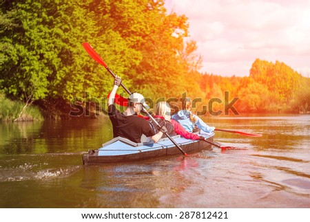 Young people are kayaking on a river in beautiful nature. Summer sunny day in outdoor - stock photo