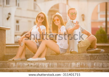 Young people are sitting outdoors, in the town, looking at the camera and showing thumbs up. - stock photo