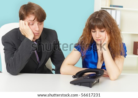 Young people are waiting for a phone call in office - stock photo