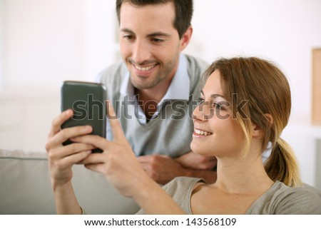 Young people at home using smartphone - stock photo