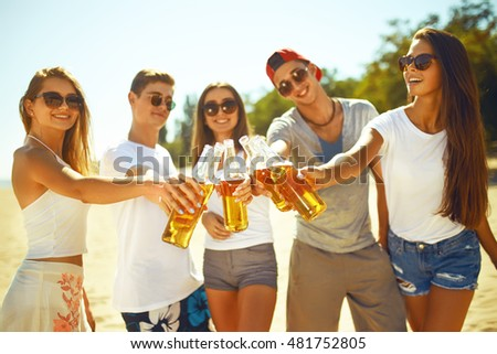 young People  clinking glasses with beer. People Celebration Beach Party Summer Holiday Vacation Concept.  enjoy summer time. Fun at the beach. Great summer mood. sunny day