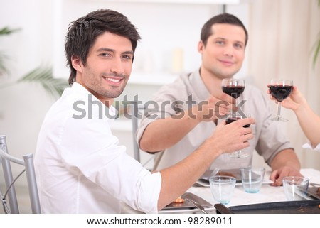 young people clinking glasses with red wine - stock photo