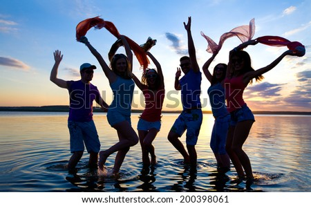 young people dancing and spraying at the beach on  beautiful summer sunset - stock photo