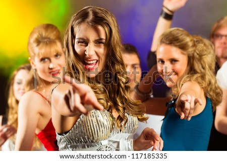 Young people dancing in club or disco and have party; the girls and boys, friends, having fun