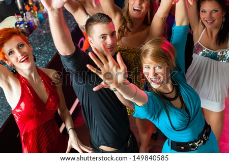 Young people dancing in club or disco, the girls and boys having fun - stock photo