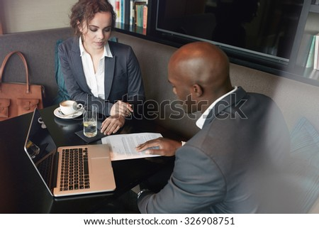 Young people discussing business strategy at cafe. Business partners meeting over coffee with documents. - stock photo