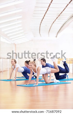 Young people do exercises in the fitness club - stock photo