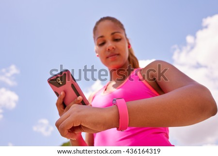 Young people doing sport activities, woman runner jogging programming fit watch and synchronizing data with mobile phone wirelessly - stock photo