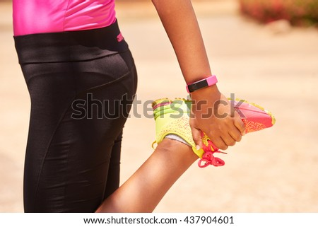 Young people doing sport activities, woman runner stretching leg using fit watch.  - stock photo