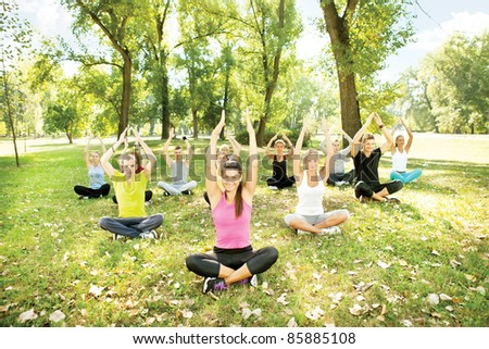 young people doing yoga exercise in park - stock photo