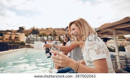 Young people drinking by the pool during party. Young friends laughing while sitting by a swimming pool. Men and women partying and having fun outdoors. - stock photo