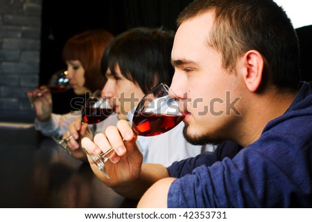 Young people drinking red wine on a bar counter. - stock photo