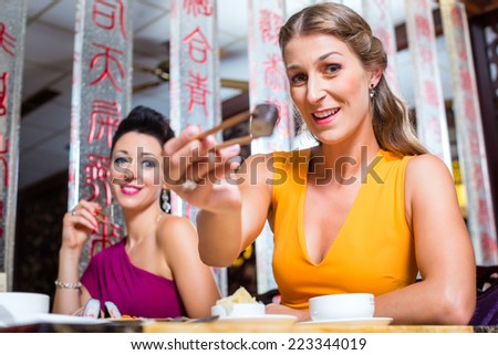Young people eating sushi in Asia restaurant
