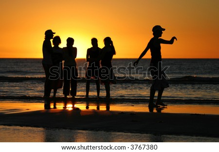 Young people enjoying sunset on the beach