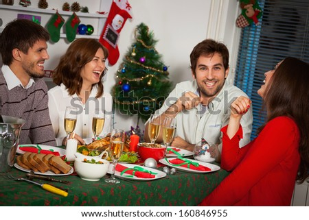 Young people gather together for Christmas dinner. - stock photo