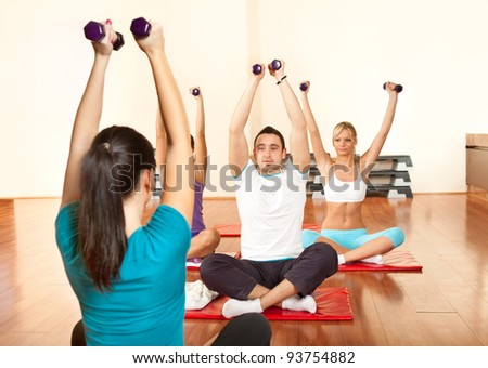 young people group doing fitness exercise with instructor - stock photo