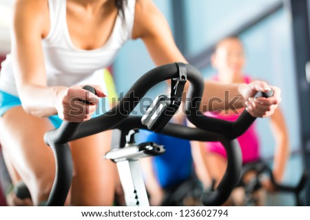 Young People - group of women and men - doing sport biking in the gym for fitness
