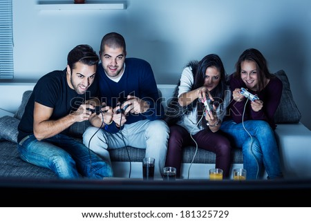 Young people having fun at night and playing video games. Selective focus - stock photo