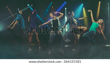 Young people having fun dancing at party in headphones. - stock photo