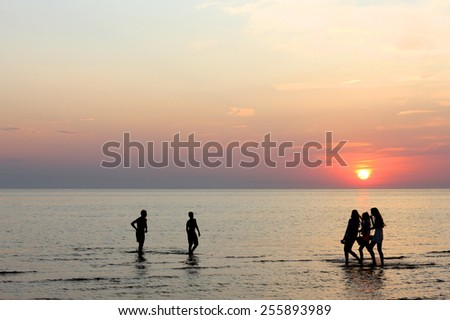 Young people having fun on the beach at sunset - stock photo
